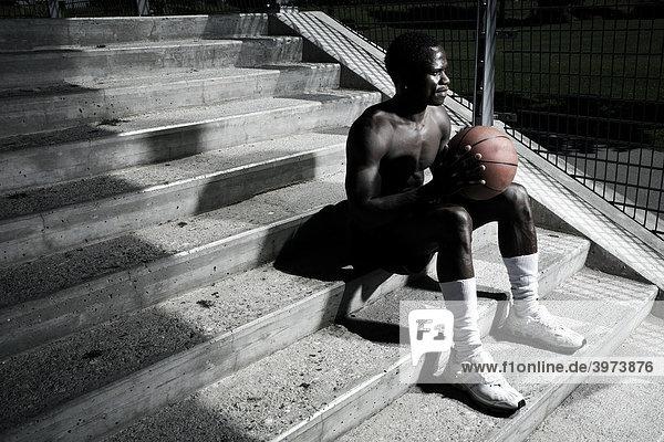 Dark-skinned basketball player sitting on stairs
