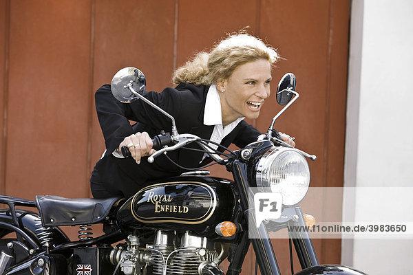 Frau im Business-Outfit mit Oldtimer-Motorrad  lacht