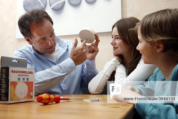 Vater erkärt seinen Töchtern den Sinn und die Funktion eines Rauchmelders für eine private Wohnung  Deutschland  Europa