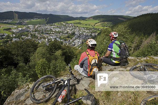 Mountainbike-Fahrer bei einer Rast am Orenberg mit Blick auf Willingen  Hessen  Deutschland