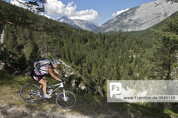 Female mountainbike rider riding through the Gleischklamm gorge  southeast of Scharnitz  Tyrol  Austria  Europe