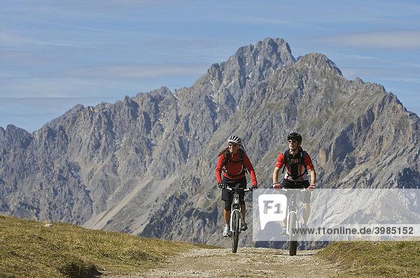 Mountainbike riders  male and female  at Hochalmsattel plateau near Karwendelhaus  alpine club house  Scharnitz  Tyrol  Austria  Europe