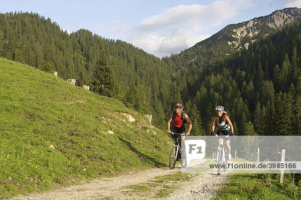 Montainbike riders  female and male  riding above the Oberbrunn Alm alpine pasture near Scharnitz  Tyrol  Austria  Europe