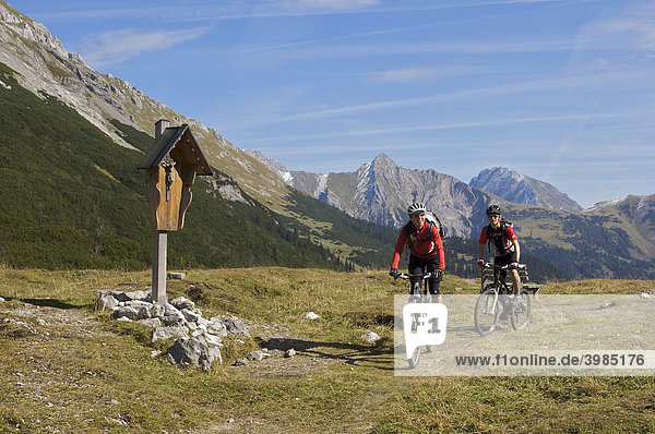 Montainbike riders  female and male  passing a wayside cross on Hochalmsattel mountain plateau  Scharnitz  Tyrol  Austria  Europe