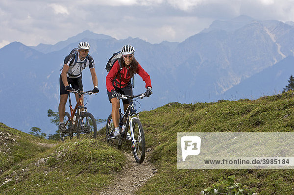 Male and female mountainbike riders on the Wallgauer Alm alpine pasture with a view towards the Karwendel Range  Wallgau  Upper Bavaria  Bavaria  Germany  Europe
