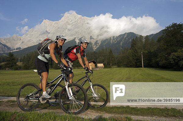 Mountainbike-Fahrerin und -Fahrer vor der Zugspitze bei Ehrwald  Tirol  Österreich