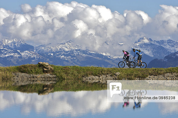 Mountain bikers,  male and female,  reflecting in the water reservoir Salvensee at Hohe Salve mountains,  Tyrol,  Austria