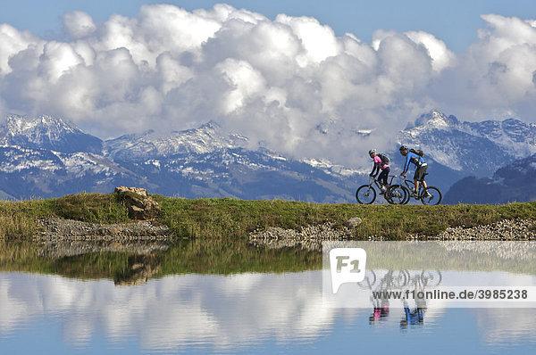 Mountainbike-Fahrerin und -Fahrer spiegeln sich im Wasserreservoir Salvensee an der Hohen Salve  Tirol  Österreich