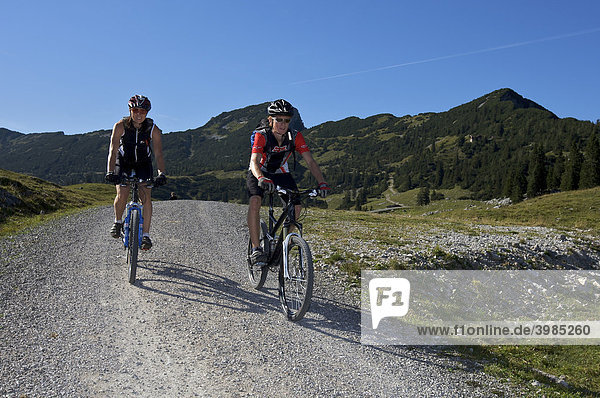 Male and female mountainbikers below the Kuhalm mountain pasture  Eschenlohe  Upper Bavaria  Bavaria  Germany  Europe