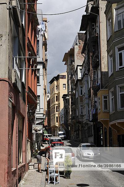 Typische Straße in Galatasarary  Restaurant mit zwei kleinen Tischen auf der Straße  Frau serviert einem Gast  Beyoglu  Istanbul  Türkei