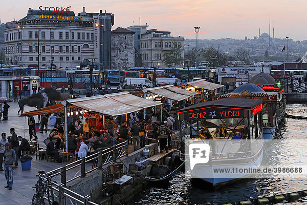 Fish sandwiches on sale in boats on the shore of the Golden Horn  evening mood  Eminoenue  Istanbul  Turkey