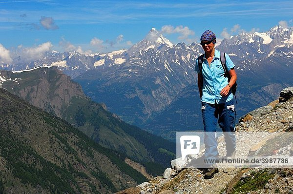 Female hiker hiking on a narrow mountain trail high above the Rhone Valley in the Pennine Alps  Valais  Switzerland
