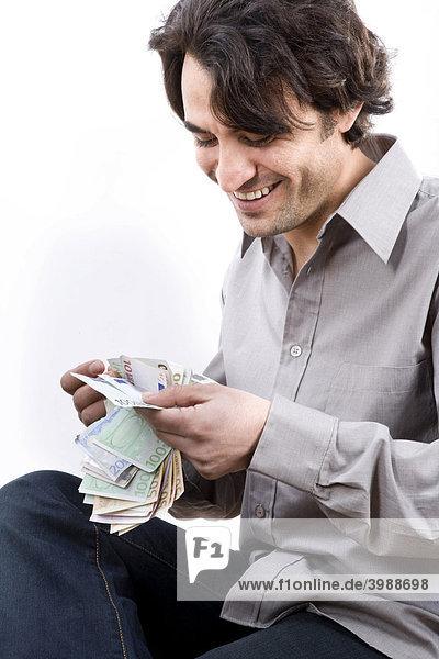 Junger Mann zählt Geldscheine