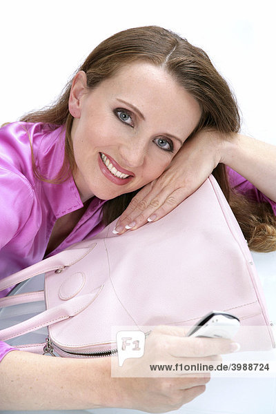 Woman wearing a pink blouse  holding her mobile