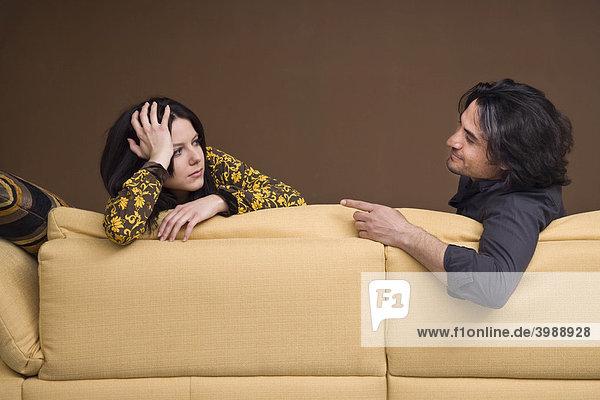 Mädchen stützt sich auf Sofa und unterhält sich mit ihrem Freund