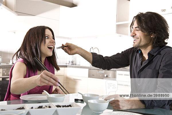Junges Paar sitzt am gedeckten Tisch und isst gut gelaunt mit Stäbchen