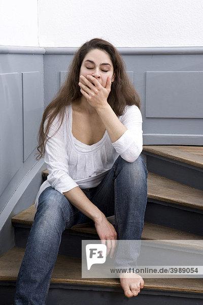 Mädchen gähnt auf alter Holztreppe
