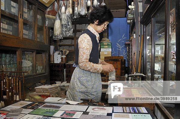 Verkäuferin wiegt kniend auf einer Tatamimatte Mineralfarben für Nihonga-Malerei ab in einem traditionellen Geschäft für Künstlerbedarf  Kyoto  Japan  Asien