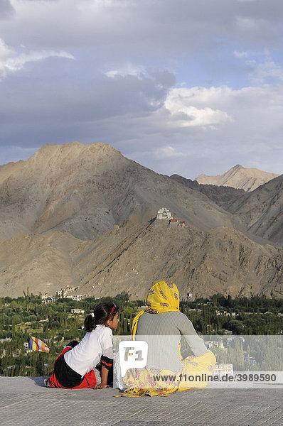 Ladakhis betrachten sich die Oase Leh mit Kloster Gonkhang und Burgruine auf dem Berg  Ladakh  Indien  Himalaja  Asien