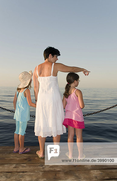 Mutter mit zwei Töchter zeigt ins Wasser