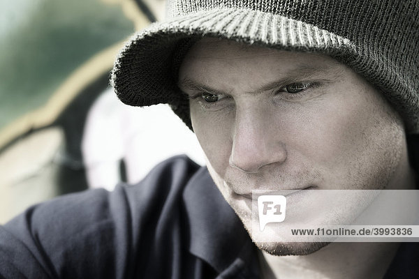 Portrait eines jungen  nachdenklichen Mannes mit Mütze vor Graffitiwand