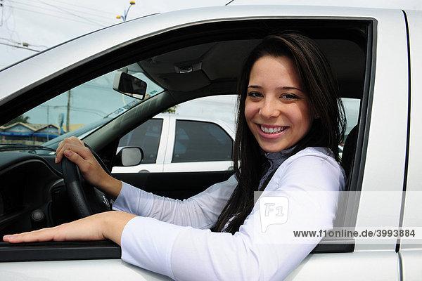 Lächelnde Frau am Steuer ihres Autos