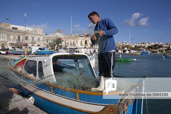 Fischer repariert sein Netz auf einem Fischerboot  Hafen von Marsaxlokk  Malta  Europa