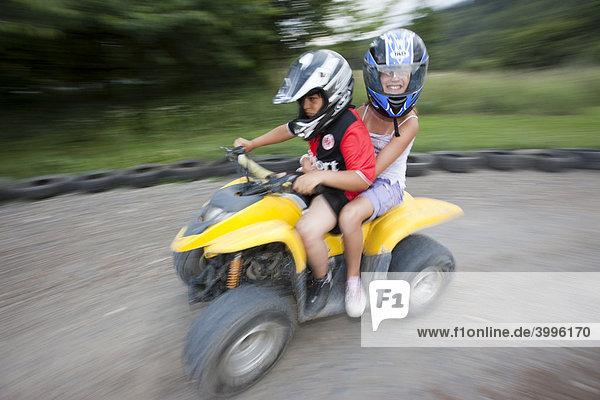 Children riding a quad bike  Hesse  Germany  Europe