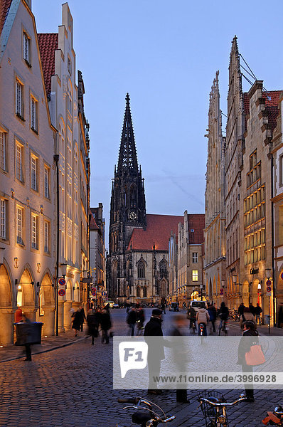 Shopping street with old  gabled houses with arcades  evening illumination  at back St. Lamberti Church  Muenster  Westphalia  Germany  Europe