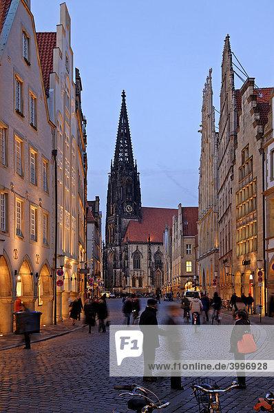 Einkaufsstraße mit alten Giebelhäusern in der Abendbeleuchtung hinten St. Lamberti Kirche  Münster  Westfalen  Deutschland  Europa