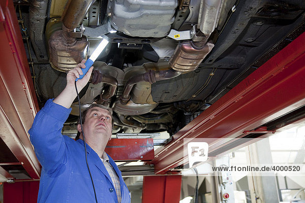 Master Craftsman of motor vehicle mechanics inspecting a car from below in a workshop
