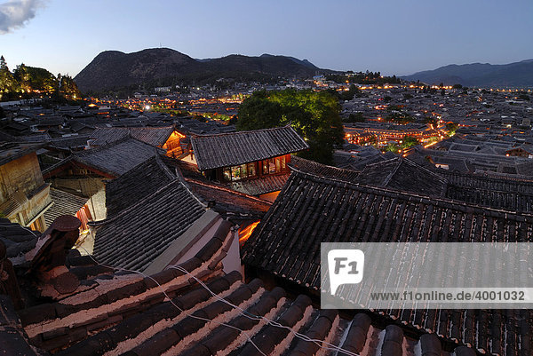 Illuminated old traditional wooden houses of the Naxi minority  in the evening  mountains in the back  Lijiang  Yunnan  Southwest China  China  Asia