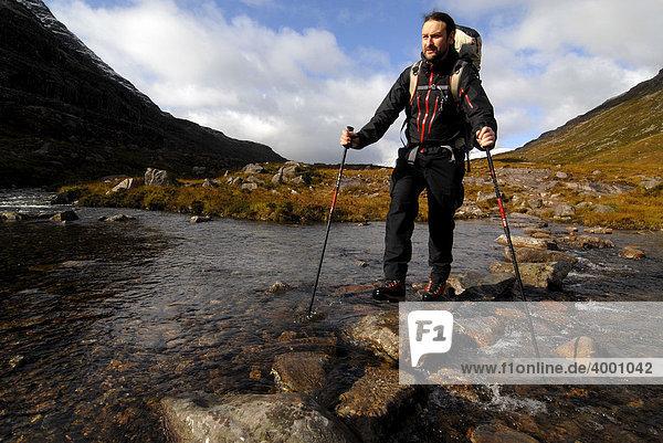 Wanderer mit Trekkingrucksack und Teleskopstöcken überquert Gebirgsfluss  Liathach  Torridon  Schottland  Großbritannien  Europa