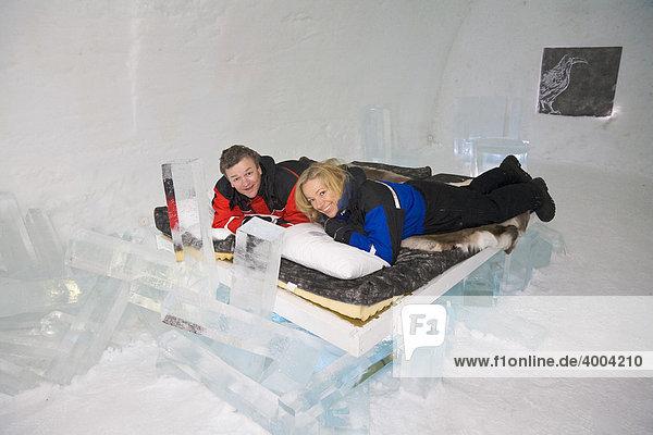 Ein Mann und eine Frau liegen auf einem Bett in einem Schlafraum des Eishotels in Jukkasjärvi in Lappland  Nord-Schweden  Schweden