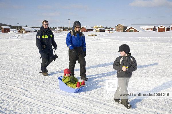 Ein Mann und eine Frau in den Vierzigern mit zwei Kindern wandern auf dem zugefrorenen Fluss Torne Aelv am Rande der Ortschaft Jukkasjärvi in Lappland  Nord-Schweden  Schweden