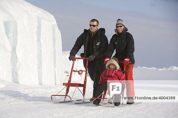 Vor dem Eishotel fahren eine Frau  ein Mann und ein vierjähriges Mädchen auf einem Schlitten  Jukkasjärvi  Lappland  Nord-Schweden  Schweden