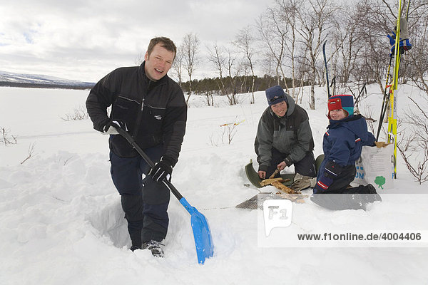 Vorbereitungen zur Grillparty in Lappland  ein Mann gräbt einen Graben in den Schnee  Frau und Kind machen Feuer in Kiruna  Lappland  Nord-Schweden  Schweden