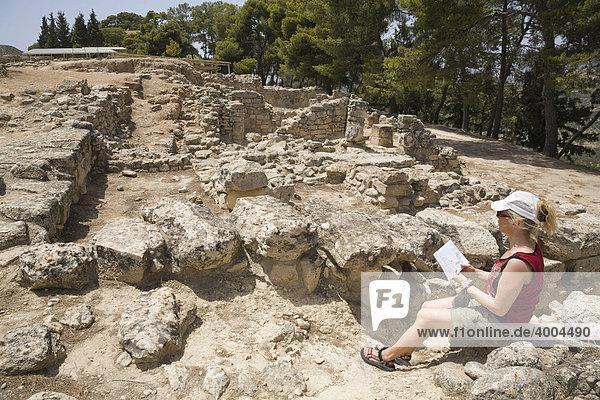 Eine Touristin sitzt inmitten der Ausgrabungsstätte der minoischen Paläste von Festos  Insel Kreta  Griechenland