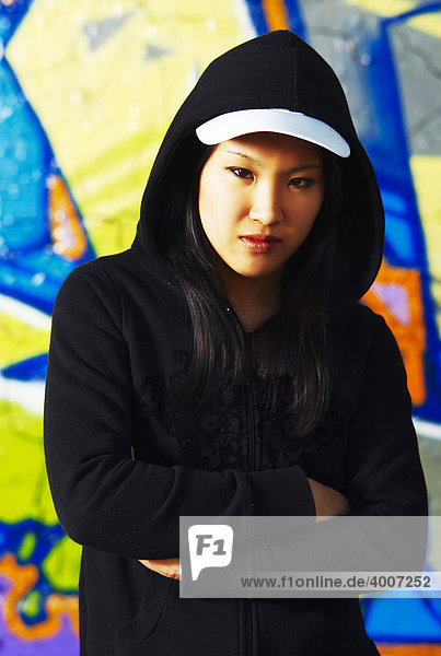 Young Asian girl in rapper pose in front of a graffiti wall