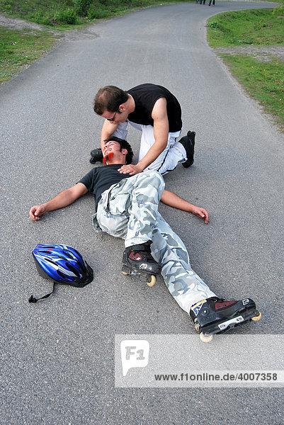 Erste Hilfe  Skater liegt nach Sturz bewegungslos auf der Straße  ein Helfer kümmert sich um ihn