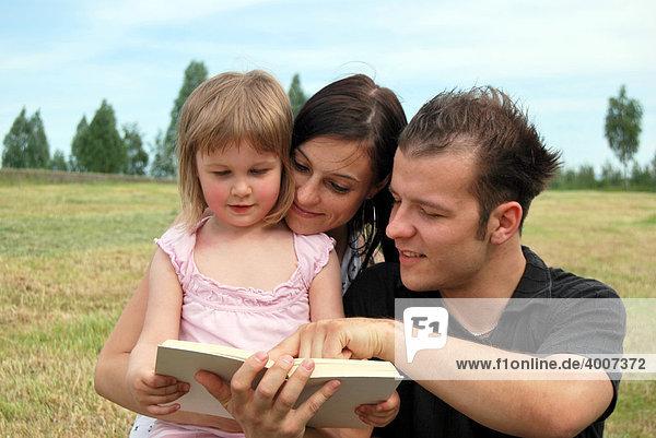 Familienglück  Mutter  Vater und Kind lesen gemeinsam ein Buch
