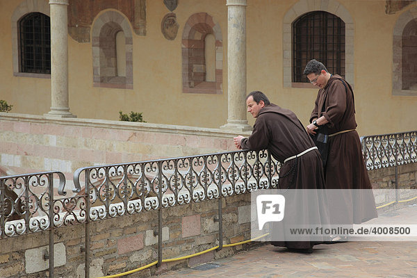 Monks in the cloister of the monastery of San Francesco in Assisi  Umbria  Italy  Europe