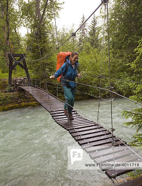 Wanderin mit Rucksack überquert eine Hängebrücke über den Taja Fluss in der Nähe der alten Stadt Canyon City  Pazifischer nordwestlicher Küstenregenwald  Chilkoot Trail  Chilkoot Pass  Alaska  USA