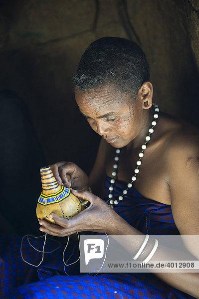 Eine Frau vom Stamm der Datooga dekoriert eine Kalebasse mit Glasperlen  Lake Eyassi  Tansania  Afrika