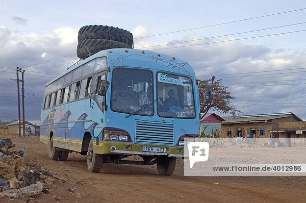 Zwei Treckerreifen wurden zum Transport unkonventionell auf das Dach eines Reisebusses gebunden in Haidom  Tansania  Afrika