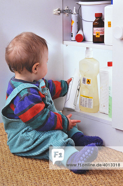 Toddler pulling cleaning agents out of an unlocked cupboard