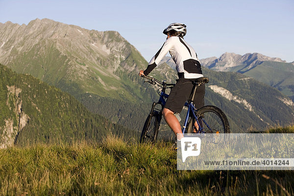 Mountain biker looking at the mountains  Zillertal Alps  Mayerhofen  North Tyrol  Austria  Europe