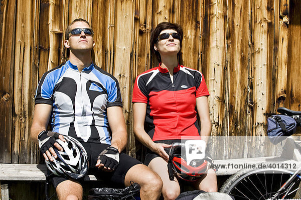 Mountain bikers taking a break in front of a hut  Alpbachtal  North Tyrol  Austria  Europe