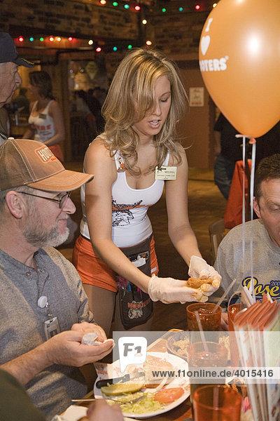 Eine Kellnerin hilft während der großen Eröffnung des Hooters-Restaurants einem Kunden bei seinem Mittagessen  Troy  Michigan  USA