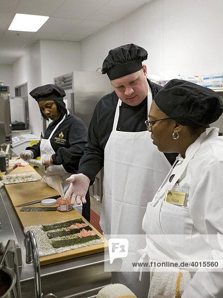 Ein Angestellter berät sich mit einer Vorgesetzten über seine Sushi-Zubereitung  Küche des Greektown Casino-Hotels  Detroit  Michigan  USA